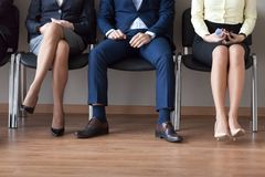 Businesspeople sitting in chairs in queue waiting job interview Royalty Free Stock Photography