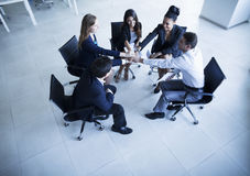 Business people sitting in a circle with hands together cheering Royalty Free Stock Photography