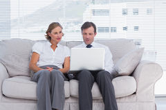 Business people sitting on couch and using laptop Stock Photos