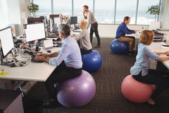Business people sitting on exercise balls while working in office. Business people sitting on exercise balls while working at desk in office stock photo