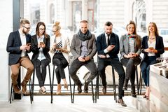 Business people sitting near the window. Business people sitting in a row using smartphones near the window in the cafe stock photos