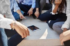 Business people sitting outside pointing at tablet. Cropped portrait of business people sitting outside pointing at tablet Royalty Free Stock Photos