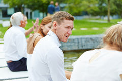 Business people sitting at pond and talking Royalty Free Stock Image