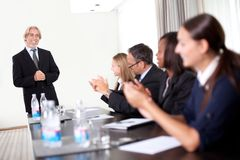 Business people sitting in a row at meeting. And celebrating goal achievement stock image