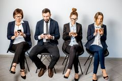 Business people sitting in a row. Business people using smart phones sitting in a row on the white wall background stock photo