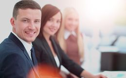 Businesspeople Having Meeting Around Table In Modern Office. Business people sitting in a row and working, focus on handsome man Stock Image