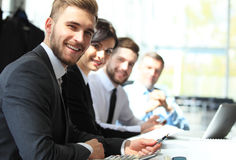 Business people sitting in a row and working, focus on young man. Business people sitting in a row and working, focus on young man stock photography