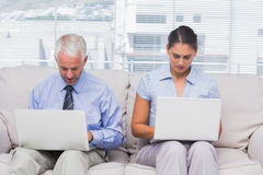 Business people sitting on sofa using their laptops Stock Photos