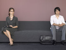 Business People Sitting On Sofa In Waiting Room stock photography