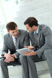 Business people sitting on stairs using tablet Royalty Free Stock Image