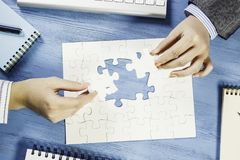 Finally finding solution. Business people sitting at table and assembling jigsaw puzzle Royalty Free Stock Photo