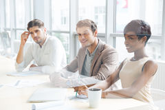 Business people sitting on training and making notes in office. Smiling young business people sitting on training and making notes in office royalty free stock image