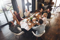 Business people sitting at a wooden table using laptops and paper document and applauding a successful concluded deal. Teamwork c royalty free stock photos