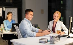 Business people with smartphone at night office royalty free stock image