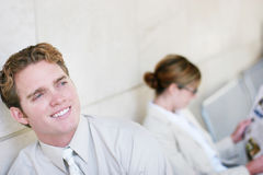Business people and smiles. Two business people sitting on bench apart from each other, the businessman smiles Royalty Free Stock Photos