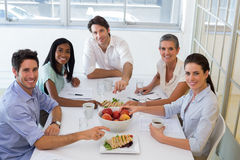 Business people smiling at camera eating sandwiches and fruit for lunch Royalty Free Stock Photos