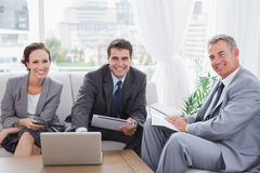 Business people smiling at camera while having a meeting Stock Images