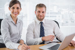 Business people smiling at camera with laptop Royalty Free Stock Photography