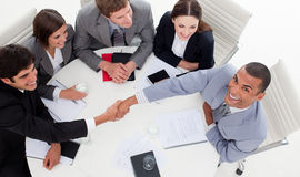 Business people smiling while closing a deal. Business people smiling at the camera while closing a deal in a meeting Stock Photo