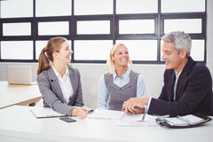 Business people smiling while discussing with client Royalty Free Stock Image