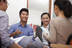 Business people smiling and having meeting in the office Stock Image