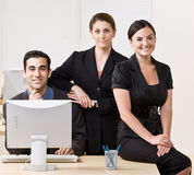 Business people smiling and posing together. Business people smiling and posing around a computer desk Royalty Free Stock Photo