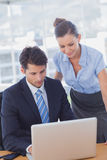 Business people smiling and working together with a laptop Royalty Free Stock Photos