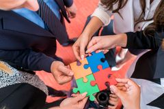 Business people solving jigsaw puzzle. royalty free stock photos