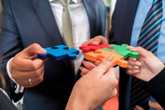 Business people solving jigsaw puzzle. Stock Photo