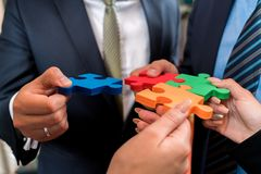 Business people solving jigsaw puzzle. Stock Image
