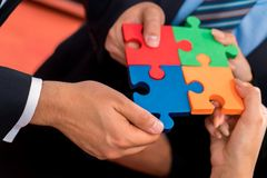 Business people solving jigsaw puzzle. Royalty Free Stock Image