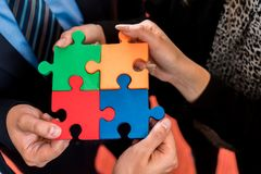 Business people solving jigsaw puzzle. Stock Photos