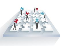 Business people solving jigsaw puzzle together Royalty Free Stock Images