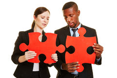 Business people solving jigsaw puzzle Stock Photo