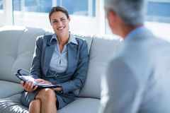 Business people speaking together on couch Stock Photo