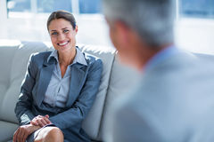 Business people speaking together on couch Stock Photography