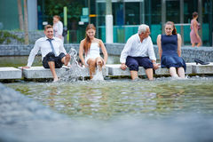 Business people splashing water with their feet Royalty Free Stock Images