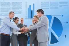 Business people stacking hands against graphs. Digital composite of Business people stacking hands against graphs Royalty Free Stock Image