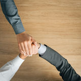 Business people stacking hands. Close up, wooden desktop on background, unrecognizable people Royalty Free Stock Photo