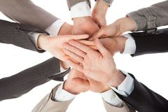 Business people stacking hands. Directly below shot of business people stacking hands against white background Royalty Free Stock Photography