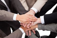 Business people stacking hands. High angle view of business people stacking hands against white background Royalty Free Stock Photo