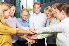 Business people stacking hands for motivation. Many business people stacking their hands for motivation next to the office stock photo
