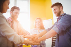 Business people stacking hands in office. Smiling business people stacking hands in creative office Stock Photo