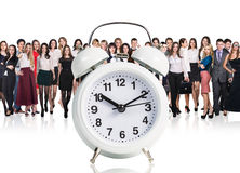 Business people stand near big alarm clock Stock Image