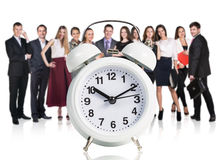 Business people stand near big alarm clock Royalty Free Stock Images