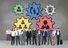 Business people standing against people in cogs graphics against grey background. Digital composite of Business people standing against people in cogs graphics Royalty Free Stock Photography
