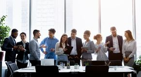 Business people standing against window, discussing work stock image