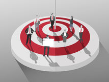 Business people standing around red and white target Stock Photo