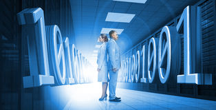 Business people standing back to back with 3d binary code in blu Stock Photos