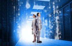Business people standing back to back in data center Stock Photography